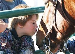 Sephanie Jones, 9, leans in to give Candlebox a kiss. Candlebox was one of eight Mustangs trained and put up for adoption Saturday at Warm Springs Correctional Center. Jones hoped to take Candlebox home with her. Photo by Brian Corley