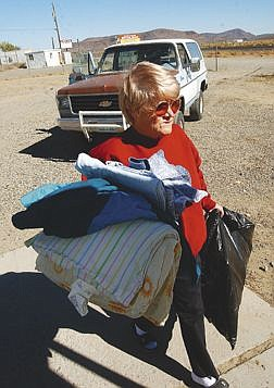 Betty McCurry carries the first donation of clothes and hangers to front of the new Lyon County FISH store. McCurry who lives just a few blocks from the store plans on volunteering time. Photo by Bran Corley