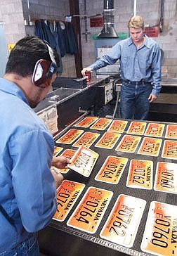 Nevada State Prison inmates Jesus Jimenez, left and David Harrington inspect Nevada license plates friday morning at the license plate shop within the prison.