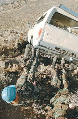 Brian CorleyNevada Army National Guard Specialist Roy Adair, left front, and Sgt. Aaron Rolston push to dislodge the Ford Bronco while Specialist Darrel Moris uses a crowbar.
