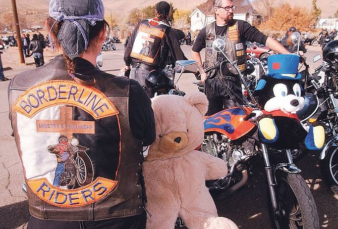 "Photo by Brian CorleyMichelle ""Peacemaker"" Fambrough, left, shows off her patch of Borderline Riders, a biker ministry, after riding in the 17th Annual Carson City Christmas Toy Run. Bikers of all walks of life delivered toys to the Carson Colony Gym on Curry Street after riding through Carson with the toys strapped to their bikes."