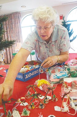 Iona Biggs sets out Christmas Tree ornaments Friday afternoon in prepartion for the Santa's Village Craft sale at the Carson City Senior's Center. Crafts and baked items will be sold Saturday and Sunday as well providing entertianment and food. Photo by Brian Corley