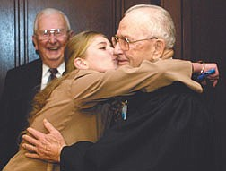 Nevada Supreme Court Justice Cliff Young, right, gets a congratulatory hug from his granddaughter Christia Young, 14, following a ceremony commemorating Young's retirement after 18 years on the bench.  Former Judge Richard Minor, rear, was one of many friends and co-workers that honored Young Wednesday morning at the court in Carson City.