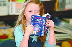 Rick GunnAshlynd Baker, an 8-year-old student at Seeliger Elementary School, dives into her new dictionary on Friday morning.