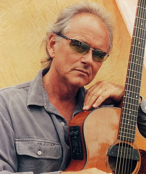 """Jesse Colin Young poses with one of the only things left in his life after a 1995 fire burned down his Point Reyes home -- his guitar. Young, who created the 1967 song of hope """"Get Together,"""" is making music again in Kona, Hawaii, and growing organic coffee. He plays at the Upstage Center Friday night."""
