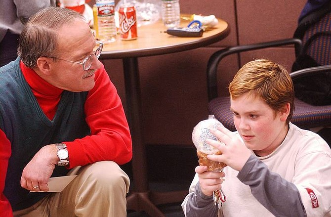 Brian CorleyJohn Lagios watches the boy he has mentored for almost a year, Adam Douglas, 10, play with a snow globe at the Mentor Center's holiday party at the South Carson Street Wells Fargo Bank Wednesday evening.