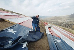 Tod Jennings talks on his cell phone to let others know about damage to the C Hill Flag while trying to shelter his son Noah Jennings, 4, from the high winds. High winds came across the top of C Hill unchecked and tore several areas of the flag apart and caused some damage to the support frame as well. Photo by Brian Corley