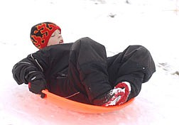 Matthew Nolan, 8, sleds down a hill along Mexican Dam Road Saturday. Photo by Brian Corley