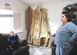North Ridge homeowner Jami Mosbacher shows the damage left behind after a vehicle careened into her home Monday morning.  Her son Christian, 5, frequently plays in that corner of the living room, Mosbacher said.