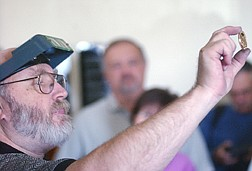 Ken Hopple, a coin press operator, holds up a coin to onlookers at the Nevada State Museum Friday. The press at the Museum was in operation minting coins for the 100th anniversary of the Gold Field Mining Camp. Photo by Brian Corley
