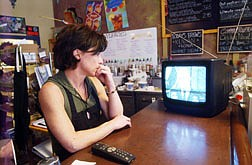 June Joplin watches a fuzzy signal from her television at work of images of Downtown Baghdad shortly after it was bombed heavily at approximately 10 am PST. Joplin's oldest son is in the Marine Corps stationed somewhere in the Persian Gulf. Her youngest son is awaiting deployment with the Army. Photo by Brian Corley