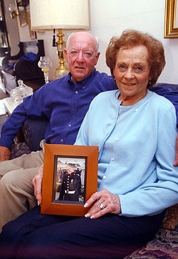 Kenneth Charipilloz Sr., left, and Alice Charipilloz hold a picture of their grandson, Sgt. Graham Collins, who has been in the Marine Corps for eight years and was deployed to the Persian Gulf two weeks ago. Collins is at least three quarters of the way to Baghdad with his unit and continues to advance on the city. Photo by Brian Corley