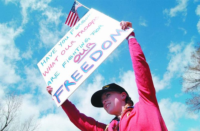 Photo by Rick GunnMeagan Long, 15, of Dayton, flies her colors in front of the Capitol on Saturday afternoon during a rally to support the troops. Long, along with her mother, Maura, organized this event, which continues today in front of the Legislative Building.