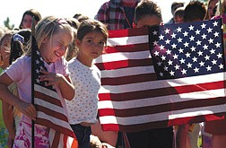 Kindergartener Shania Hicks,6, giggles during  a flag ceremony at Fremont School Tuesday morning. Standing next to her i  Elizabeth Bracamontes, 6,  and Brandon Iza, 7,  behind flag.