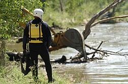 A Search and Rescue team member watches the waterTuesday morning while a backhoe clears a dense debris field from the Carson River location where a Dayton man went missing.   photo by Rick Gunn