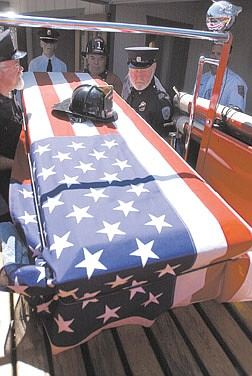Paul Webster, from left, and Don Blanchard, of Warren Engine Fire Co. No. 1, lift the casket of Dean Cheney into one of the company's fire trucks.