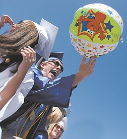 Carson graduate Jack Brooks, 18, tips an Elmo beach ball across the aisle during graduation ceremonies at the school's football field.
