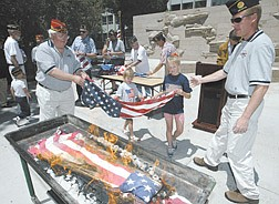 American Legion member Ron Gutzman, left, helps his granddaughters Deelany Grant, 6, and Jazmin Grant, 9, place a retired flag into the fire during the annual Boys State flag retirement ceremony on Thursday.  Tim Tetz, the director of Boys State, right, says each flag is retired in ceremony because each has meaning.