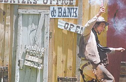 """Dan Cole, 22, of Reno, runs into the bank with a stick of dynamite Saturday at Mills Park. Cole plays the part of a bad guy in the """"Gunfighters Show"""" at the Carson Rendezvous."""