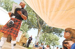 """Robert Bledsaw """"The Pipin' Padre,"""" preaches during morning mass on the main stage at the Carson Rendevous Sunday.  Alisha Kingsley, 10, of Carson, and her mother Dorrie listen to the sermon."""