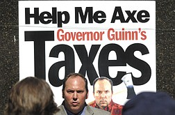 George Harris, founder of the Axe The Guinn Tax Ralley stands in front of a poster with his picture on it during the anti-tax ralley that took place in front legislature Wednesday afternoon .