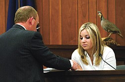 Alane Dockstader former girlfriend of murder suspect Chris Fieghan, looks over evidence from defense attorney Richard Young during Fieghans murder trial  in Douglas County on Thursday. Fiegehen stands accused of killing Dockstader's stepfather and shooting her mother Feb. 10, 2002.