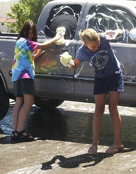photo by April HeathElise Sala, left, and Katy Runde, both 13, keep cool in the mist during a car wash Wednesday to benefit the Carson City Recreation Department's Trailblazers Summer Kamp program.