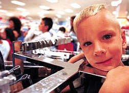 Shawn Miller, 7, of Gardnerville, plays in a Levi Jean rack at Mervyn's during the store's ChildSpree event Saturday.