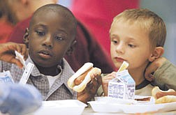 Tyear Brown-Bray, 6, left, and Byron Eddie, 6, get down to the business of lunch at Mark Twain Elementary's  first day of school Tuesday.  photo by rick Gunn