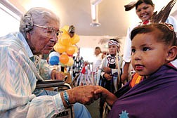 Wiona James shakes Tawanee Ackley's hand while Ackley's dance group the Mason Valley Wind Spirit dance at James' 101st birthday party at Stewart Community Center Saturday. | photo by Brad Horn