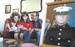 Marine Cpl. Larry Brown's family look through photos of his welcome home party held over Labor Day weekend after his 7-1/2 month deployment in Iraq.  From left, Brown's sister Karri Couste, mom Sally Brown-Bliss and step-father Dean Bliss, at their Carson CIty home on Wednesday, say Brown will be getting out of the Marines in November.