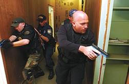 Luke Elliott, of The Walker River Police Department , right,     prepares to enter a room at the Stewart facility during a Counter Drug Task Force Training in Carson City Thursday. Ellliott was flanked by Carson City Sheriff's Deputy Jason Gault, Nevada Highway Patrol State Trooper Paul Hales , and  and Bret Allred of Iron City Utah. | photo by Rick Gunn