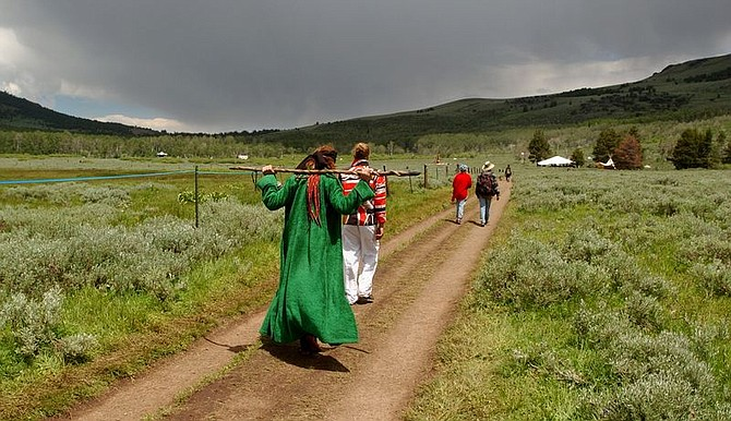 **  ADVANCE FOR SUNDAY JULY  4  ** Rainbow Family participants walk on a path which separates villages Wednesday, June 30, 2004, in the Modoc National Forest, Calif. The remote counterculture event culminates Sunday as thousands of hippies and followers of unorthodox religions hold hands in a circle and silently pray for world peace from dawn until noon. (AP Photo/Ben Margot)