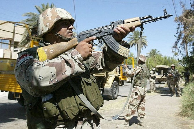 Iraqi National Guard soldiers cover the street while conducting a weapons raid on a home in Baghdad, Iraq, Saturday, July 3, 2004. For the first time, the 303rd Iraqi National Guard Battalion led the raid, supported by U.S. Army soldiers from the 1st Cavalry. (AP Photo/Jim MacMillan)
