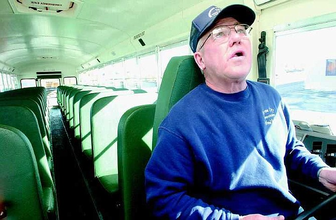 Rick Gunn/Nevada Appeal Carson City School District Bus Driver Larry Bruntz does a safety check on his bus before gassing up.