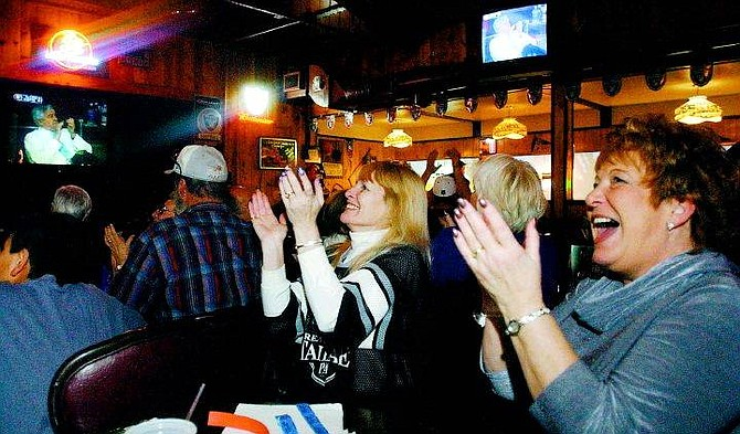 BRAD HORN/Nevada Appeal Carson City Raider Booster treasurer from right Nancie (Michael) Pitts and secretary Leni (Peyton) Manning cheer after a 50-yard field goal by Carolina Panther kicker John Kasay right before the half ended Sunday at Joe Bob's Chicken in Carson City.