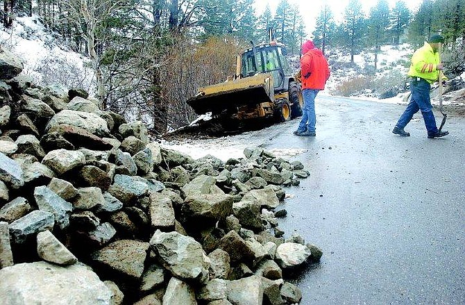 Rick Gunn/Nevada Appeal Carson City road workers pack fill dirt into a section of Old Clear Creek Road Thursday afternoon eroded during a recent storm.