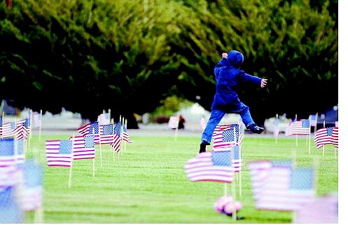 Brad Horn/Nevada Appeal Noah Jennings, 5, of Carson City, jumps over American flags just placed on gravesites of veterans at the Lone Mountain Cemetery in Carson City on Friday.