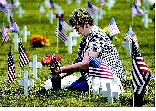 Cathleen Allison/Nevada Appeal Linda Wilson, of Carson City, puts fresh roses on her husband Donald's grave at the Lone Mountain Cemetery Monday.  Wilson served as an Army medic and was one of many veterans honored during Memorial Day ceremonies around the country.