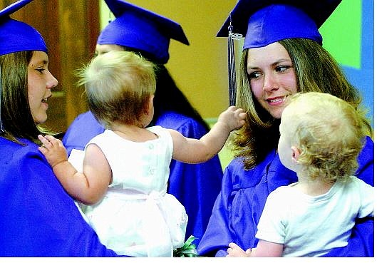Rick Gunn/Nevada Appeal K.C. Pierson, 19, and her 10-month-old daughter, Akira, visit with Shay Olsen, 19, and her 18-month-old daughter, Alyssa, while waiting for Pioneer High School graduation to begin. The alternative high school graduated 37 students Tuesday evening at the Brewery Arts Center Performance Hall.