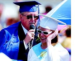 Glen Adair speaks to the graduating class after Charity Ricks and Maria Urbina presented their principal a cap and gown on his last official day of duty during graduation  ceremonies on the football field Saturday.  BRAD HORN Nevada Appeal