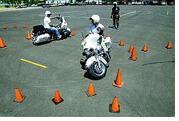 Cathleen Allison/Nevada Appeal Carson City sheriff's motorcycle officers Sgt. Mike Cullen, left, and Deputy Bill Richards practice for the upcoming Fun Run on Friday and Police Motor Competition on Saturday at Mills Park. Deputy Wayne Wheeler, rear, is also competing.