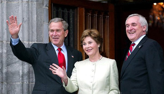 US President Bush and first lady Laura Bush wave with Irish Prime Minister Bertie Ahern, right, at Dromoland Castle in Co. Clare western Ireland Friday June 25, 2004 at the start of the European Union/US summit meeting. The EU/US meeting runs until Saturday. (AP Photo/Martin Cleaver )
