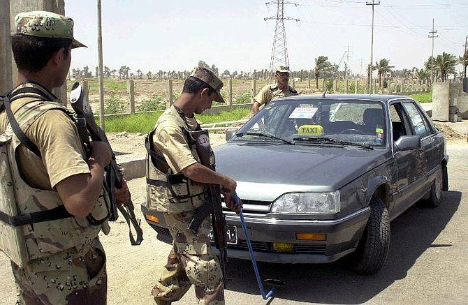 Members of the Iraqi Civil Defense Corps stop cars at a checkpoint leaving Hillah, south of Baghdad, Iraq, Monday, June 28, 2004. (AP Photo/Mohammed Uraibi)