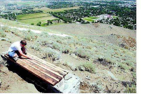 Brad Horn/Nevada AppealRyan Keating, 15, of Carson City and 16 other Scouts and volunteers built this bench at the top of C-Hill Saturday. Keating, above, and his father, Ryan; Ed and Nathan James; and Chris Bradley finished the Carson High School student's Eagle Scout project Sunday morning.