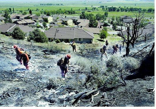 Cathleen Allison/Nevada Appeal Firefighters from a Stewart Camp crew continue to mop up the Vittori Fire near Coleville, Calif., Tuesday. Firefighters were able to protect the Coleville Marine housing area from the quick moving blaze that ignited Monday afternoon.