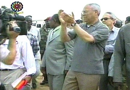 """In this image from televsion Secretary of State Colin Powell claps as he and his group approaches a group of villagers in Al-Fasher, in the western province of Darfur in the Sudan, Wednesday, June 30, 2004. Powell came to tour camps and press the government to end ethnic violence and a humanitarian crisis he has called """"catastrophic."""" (AP Photo/Sudanese TV via APTN)"""