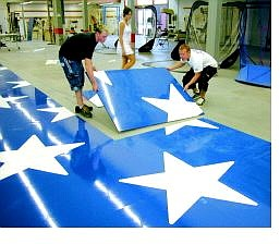 Employees of Sign Designz piece together plates that, when completed, will make up the new C Hill American flag. Pictured from left are Jeremy Buscay, Brittany McClelland and Josh Buscay.   SETH MEYER Nevada Appeal