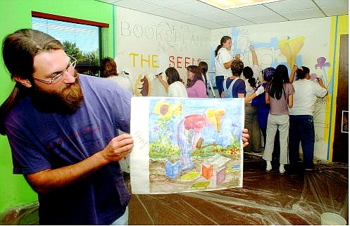 SETH MEYER/Nevada Appeal Cory King, youth services librarian at the Carson City Library, holds up the illustration done by Dale Mower on which the new library mural is based.