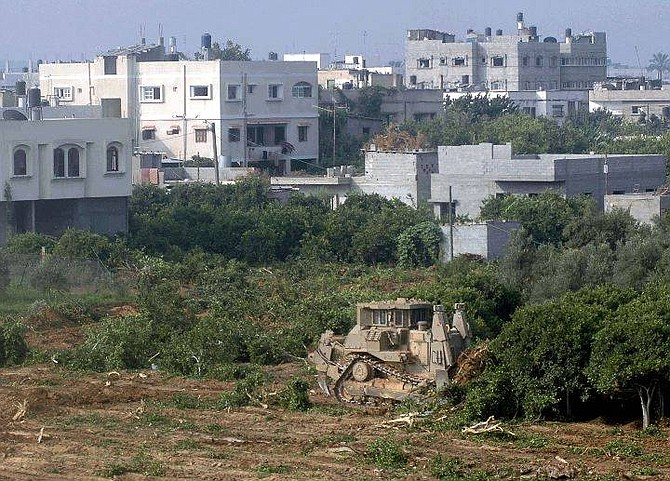 An Israeli army bulldozer uproots orange trees in the outskirts of the northern Gaza town of Beit Hanoun, background, as fighting goes on in the city during a major Israeli army incursion Thursday July 8, 2004.  Israeli troops and Palestinian gunmen fought fiercely in Beit Hanoun Thursday. At least six Palestinians, among them three militants and a 35-year-old woman, have been killed, Palestinians and the Israeli army said. (AP Photo/Hatem Moussa)